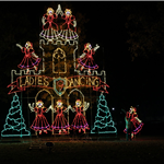 Image of light display for Trail of Lights depicting the 9th Day of Christmas with 9 Ladies Dancing